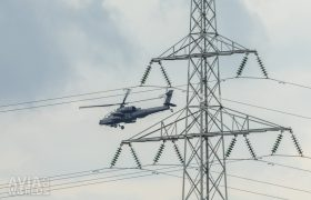 AH-64D Apache behind a transmission tower