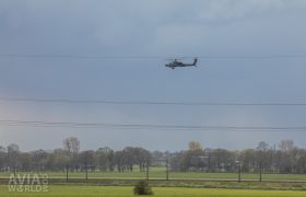 AH-64D Apache behind overhead power lines