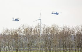 Two Boeing AH-64D Apaches and a wind turbine