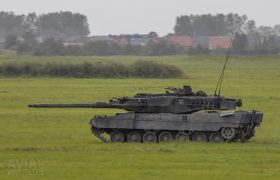 Fast moving Leopard 2A6MA2 in front of a village